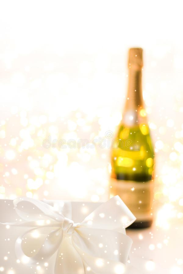 New Years Eve holiday champagne bottle and a gift box and shiny snow on marble background. Christmas time, happy holidays and luxury present concept - New Years royalty free stock photo