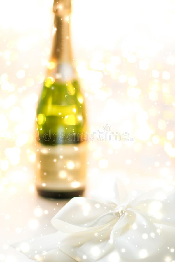 New Years Eve holiday champagne bottle and a gift box and shiny snow on marble background. Christmas time, happy holidays and luxury present concept - New Years royalty free stock images
