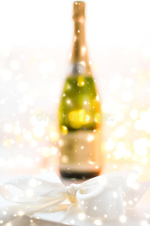 New Years Eve holiday champagne bottle and a gift box and shiny snow on marble background. Christmas time, happy holidays and luxury present concept - New Years stock images