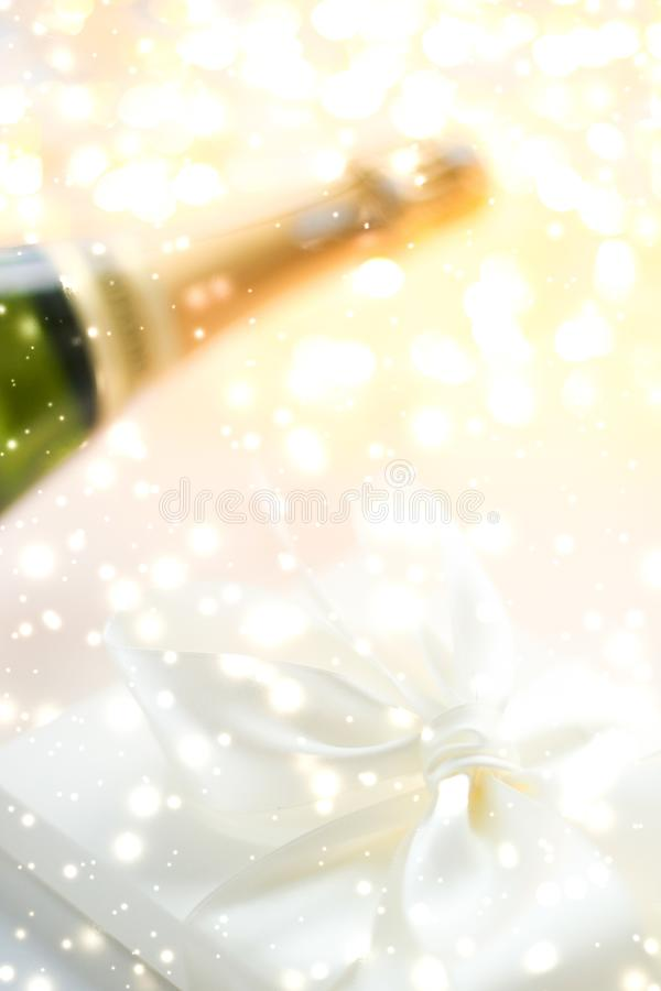New Years Eve holiday champagne bottle and a gift box and shiny snow on marble background. Christmas time, happy holidays and luxury present concept - New Years royalty free stock image