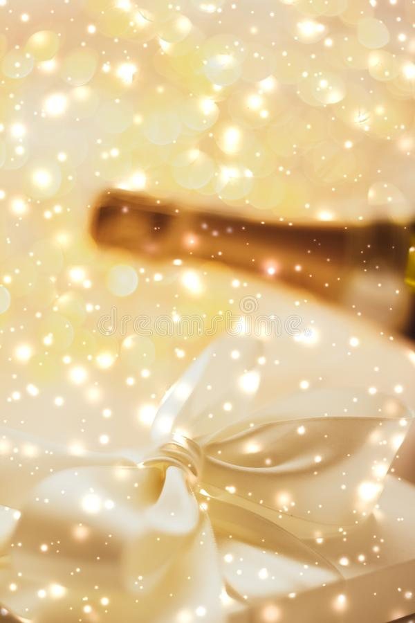 New Years Eve holiday champagne bottle and a gift box and shiny snow on marble background. Christmas time, happy holidays and luxury present concept - New Years stock photos