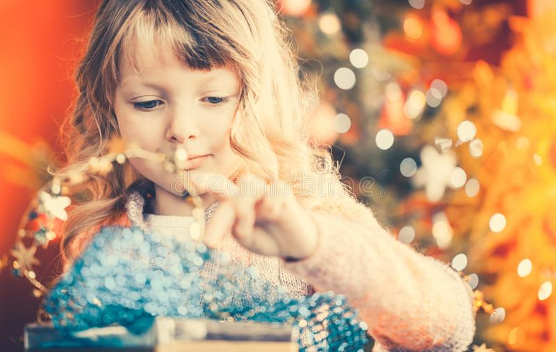 Christmas, happy little girl with Xmas present on Christmas Eve royalty free stock photos