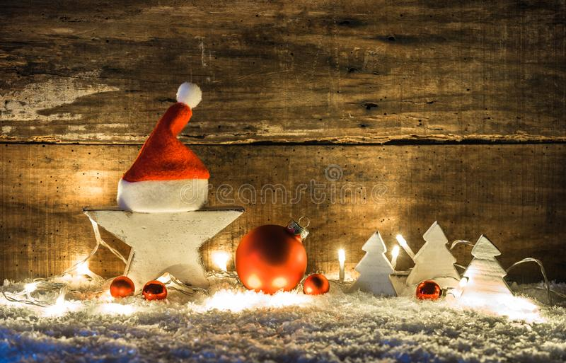 Christmas time holiday season background with white wooden star decorated with santa cap, balls, christmas trees and lights. Decoration on snow stock image