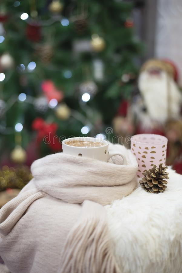 Christmas time. Hot chocolate, a cup of cappuccino on a fur chair in front of a large Christmas tree with balls and lights. Warm stock image