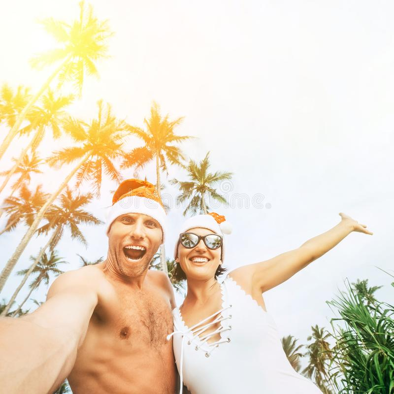 Christmas time image of Cheerful young people couple dressed re. D Santa hats making selfie with tropic palm trees background royalty free stock image