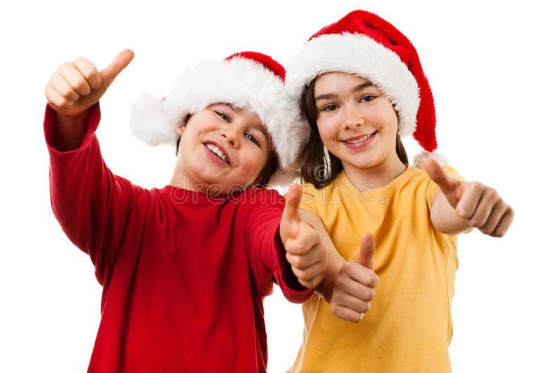 Christmas time - girl and boy with Santa Claus Hat showing OK sign. Christmas time - kids with Santa Claus Hat showing OK sign stock image