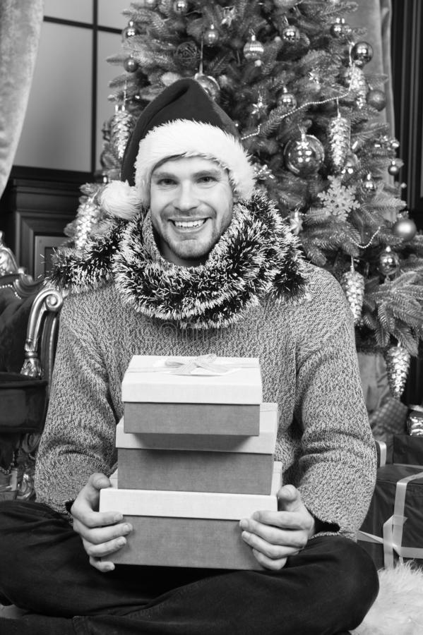 Christmas time. Man in santa hat hold xmas presents. Happy man with xmas gift boxes. Guy is celebrating Christmas at stock image
