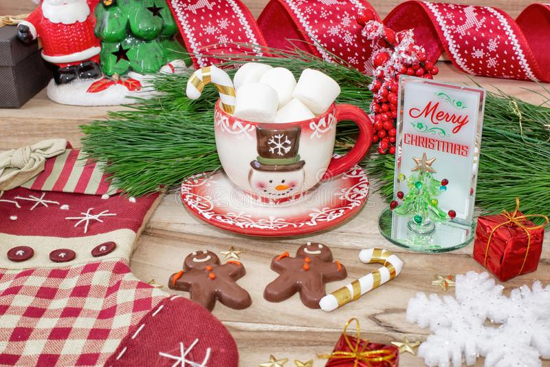 Christmas time. A mug with a snowman, marshmallow and gingerbread cookies on a wooden table is decorated with Christmas decoration royalty free stock images