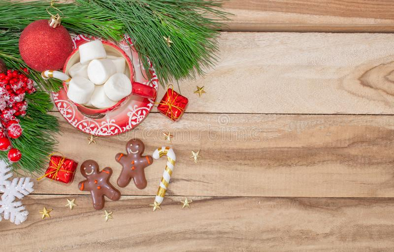 Christmas time. A mug with a snowman, marshmallow and gingerbread cookies on a wooden table is decorated with Christmas decoration stock photos