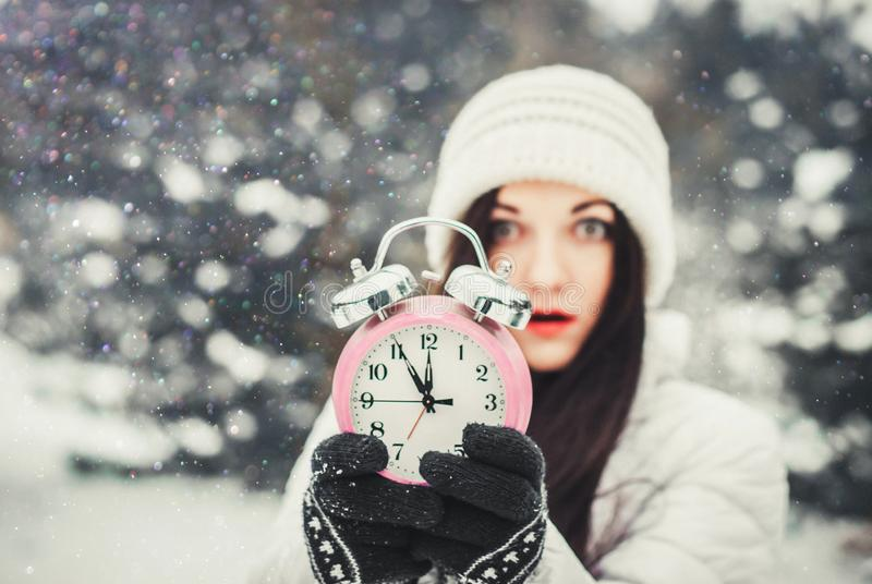 Christmas time and new year`s eve concept. Smiling surprised woman holding alarm clock and pointing at it. Christmas time and new year`s eve concept. Smiling royalty free stock photo