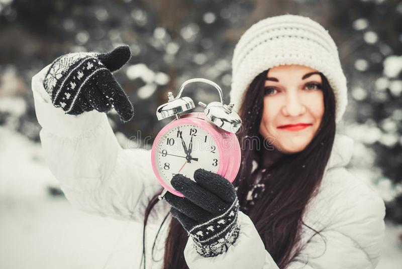 Christmas time and new year`s eve concept. Smiling surprised woman holding alarm clock and pointing at it. Christmas time and new year`s eve concept. Smiling royalty free stock photos