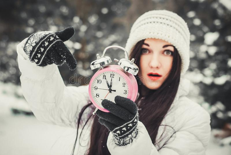 Christmas time and new year`s eve concept. Smiling surprised woman holding alarm clock and pointing at it. Christmas time and new year`s eve concept. Smiling stock photo