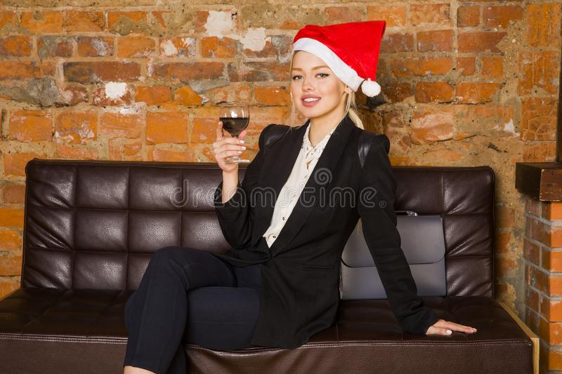 Christmas time in office. Young beautiful blond business woman on leather couch. Business concept. royalty free stock photos