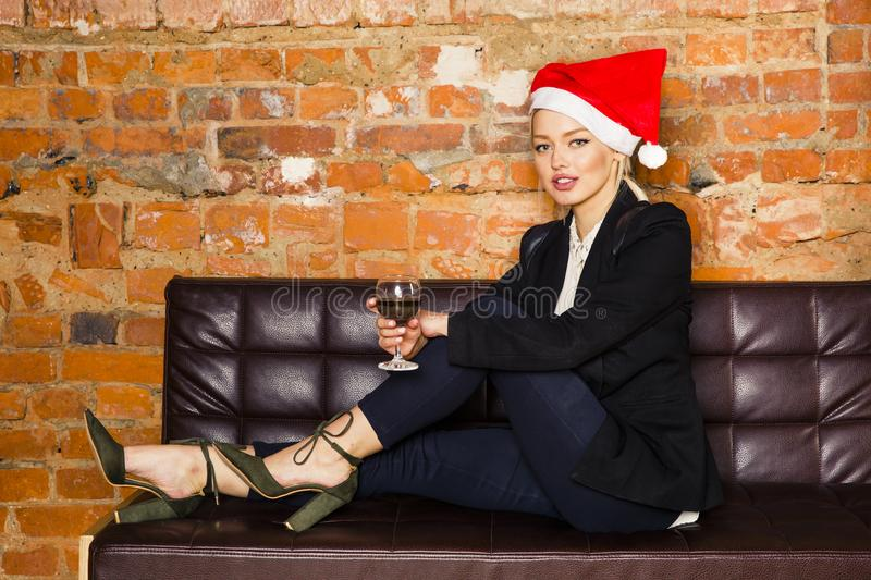 Christmas time in office. Young beautiful blond business woman on leather couch. Business concept. royalty free stock photo