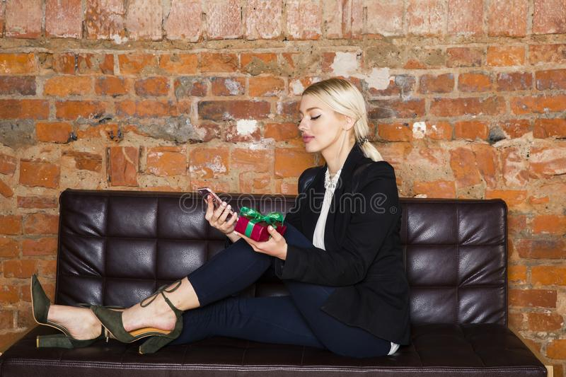 Christmas time in office. Young beautiful blond business woman on leather couch. Business concept. stock photos