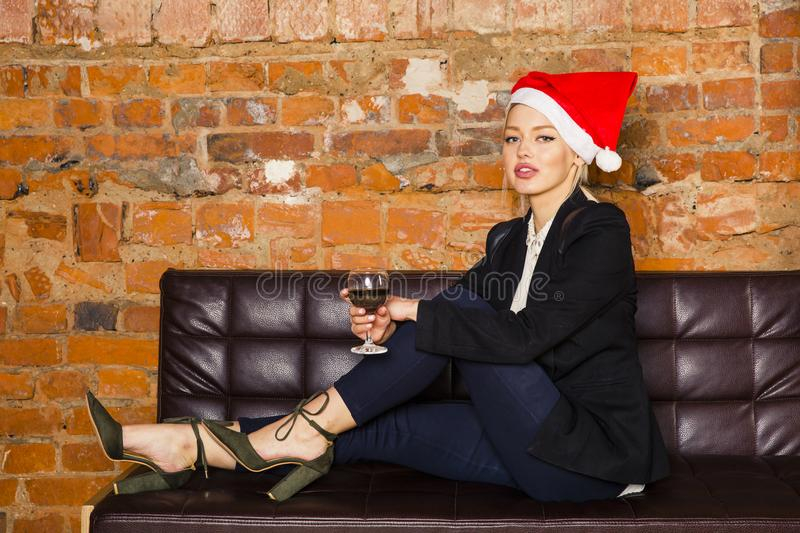 Christmas time in office. Young beautiful blond business woman on leather couch. Business concept. royalty free stock image