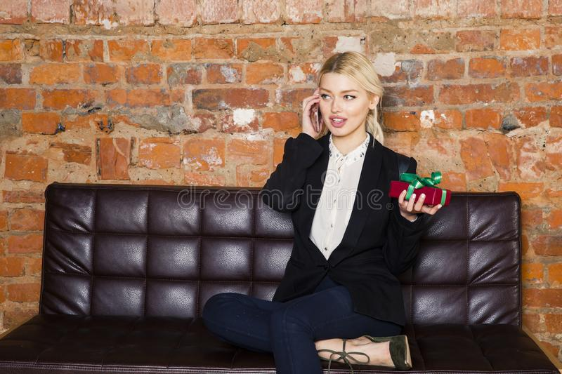 Christmas time in office. Young beautiful blond business woman on leather couch. Business concept. stock photo