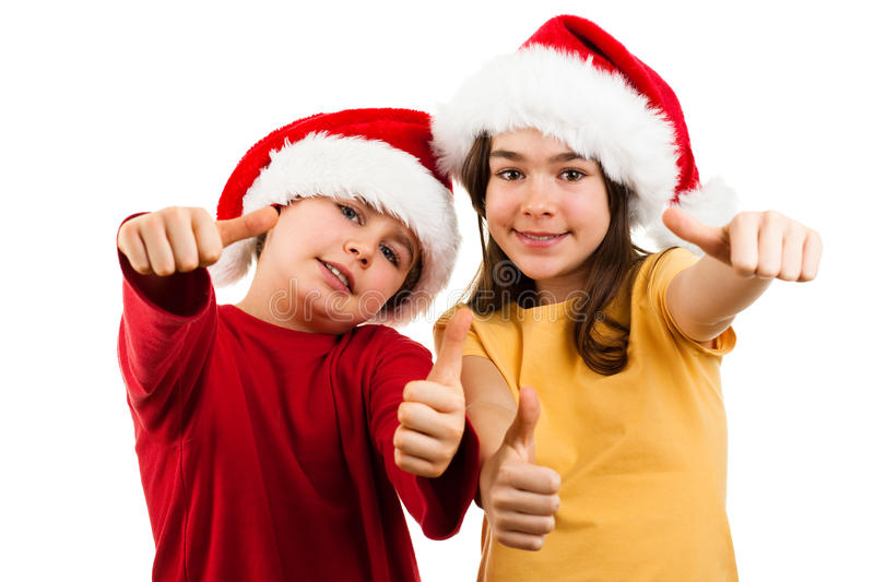 Christmas time - OK sign. Christmas time - girl and boy with Santa Claus hat isolated on white background royalty free stock photography