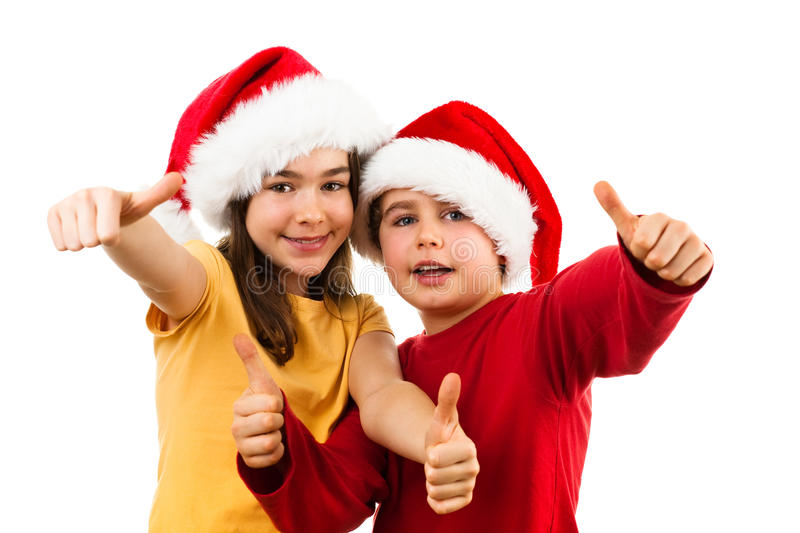 Christmas time - OK sign. Christmas time - girl and boy with Santa Claus hat isolated on white background stock photography