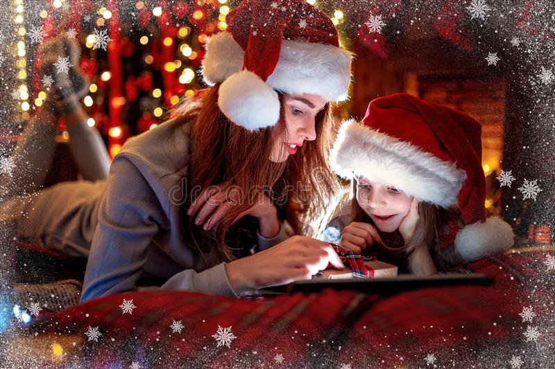 Smiling family mother and daughter in santas hats and pajamas watching funny video or choosing gifts on digital tablet royalty free stock images