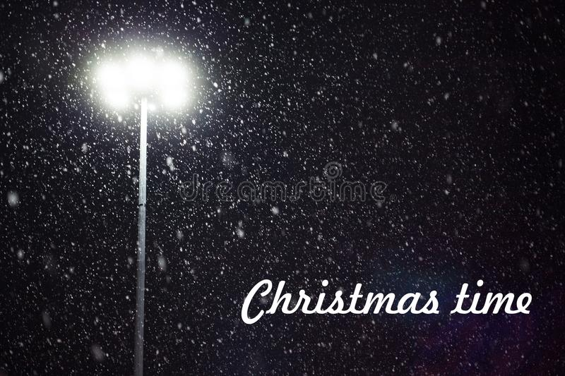 Christmas time. Snow falling in the light of a lantern stock photography
