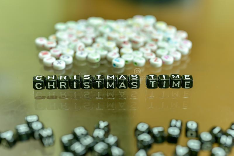 CHRISTMAS TIME written with Acrylic Black cube with white Alphabet Beads on the Glass Background.  stock image