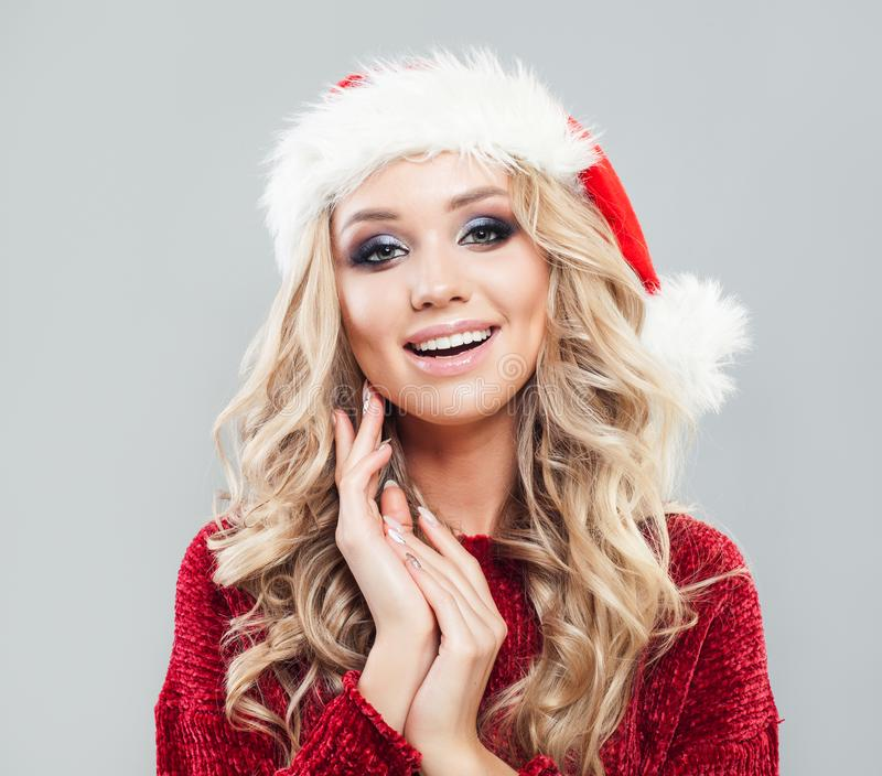 Christmas time. Young smiling woman wearing santa claus hat stock photo