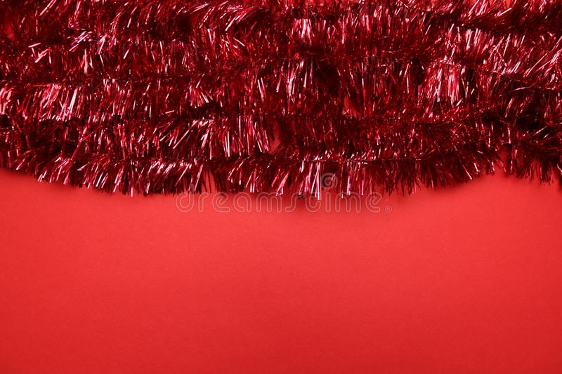 Christmas tinsel frame with sparkles on a red background stock photo