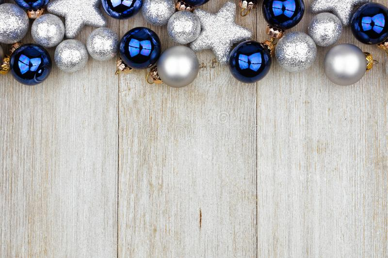 Christmas top border of blue and silver ornaments on gray wood royalty free stock images