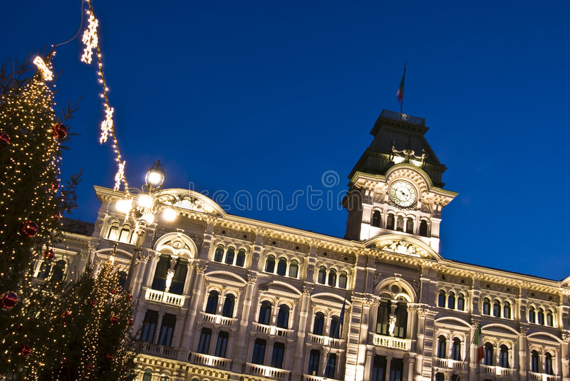 Christmas Town Hall. Piazza Unità d'Italia with illuminated Town hall and buildings with christmas lights decorations and trees at dusk / night - Trieste stock image