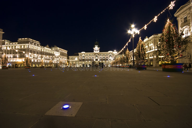 Christmas Town Hall. Piazza Unità d'Italia with illuminated Town hall and buildings with christmas lights decorations and trees at dusk / night - Trieste stock photos