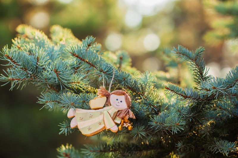 Christmas toy - beautiful wood angel on green spruce and lights background. Place for text. royalty free stock images