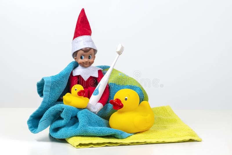 Christmas toy elf with electric toothbrush and accessories for bath on white background stock photo