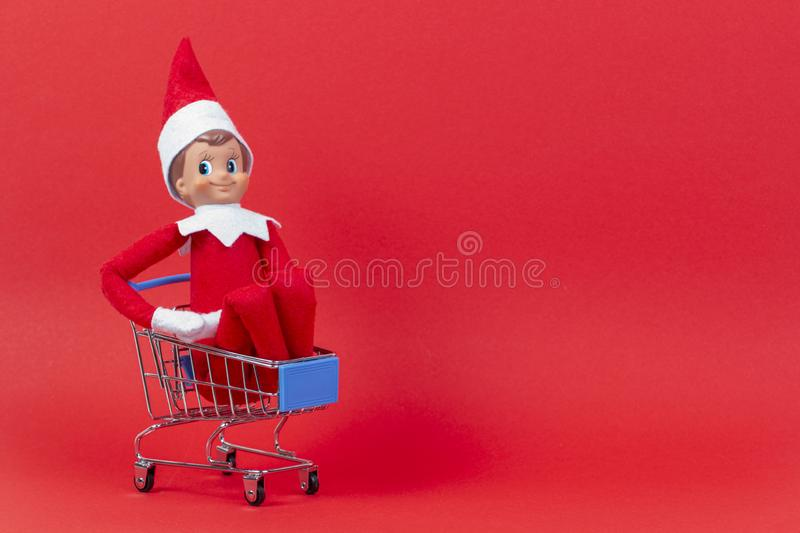 Christmas toy elf on shelf sitting in mini shopping cart on red background royalty free stock photos