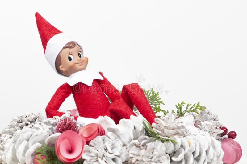 Christmas toy elf sitting in the middle of light christmas wreath royalty free stock images