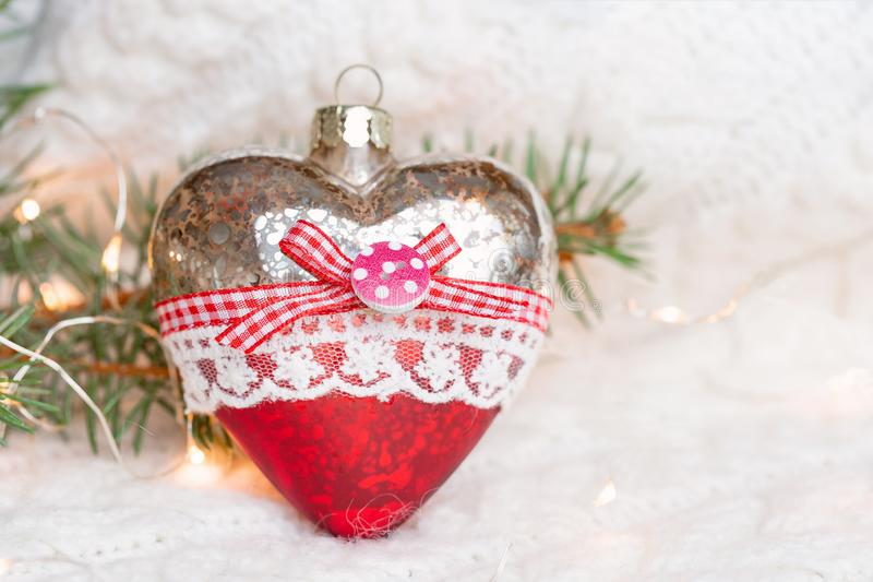 Christmas toy heart on a white knitted warm sweater surrounded by garlands. stock photography