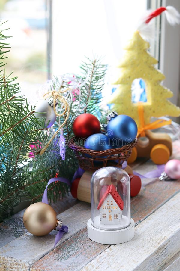 Christmas toy house, balls, cones, branches of spruce, illumination on a wooden surface on a background of a window stock photography