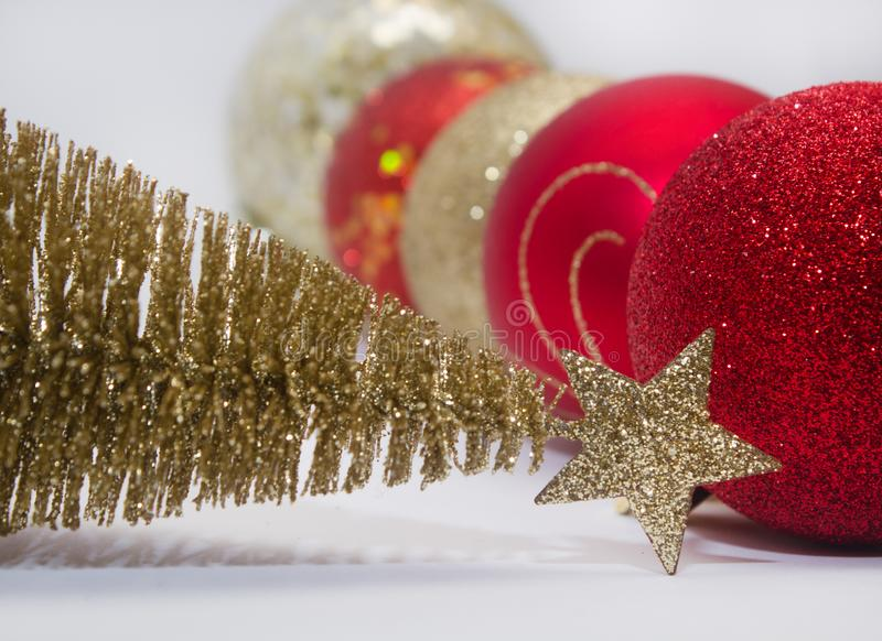 Christmas toy, a lot of shiny red, gold and silver balls and golden tree. New Year. On a gray background. Side view stock photos