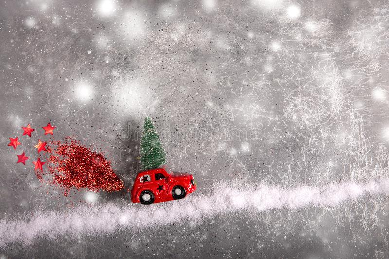 Christmas toy red car with fir tree on the roof on snow road with red sequin smoke. Flat lay stock images