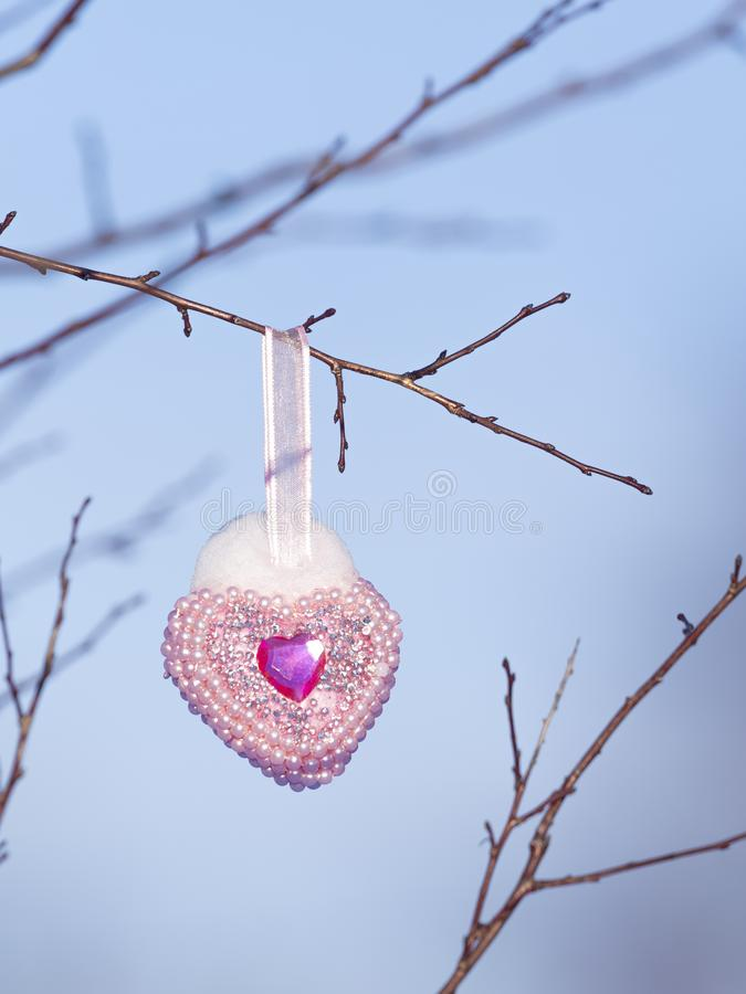 Christmas toy and snow on it. Christmas toy in the form of a pink-purple heart with pearls hanging on a bare tree branch and snow on it against a blue sky royalty free stock image