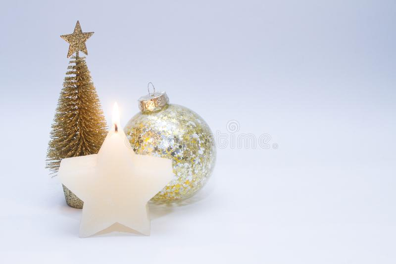 Christmas toy, tree, ball of golden color and a burning candle. New Year. On a gray background royalty free stock images