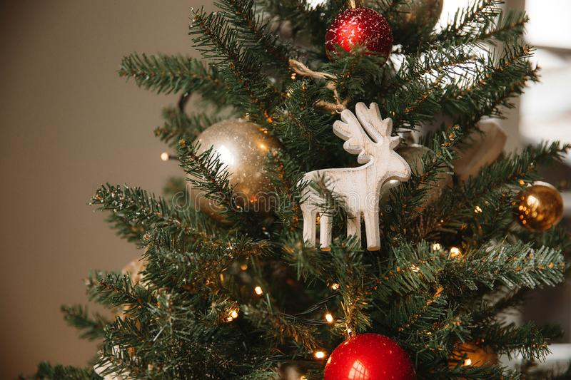 Christmas toy wooden deer on the Christmas tree. Near the window royalty free stock photo