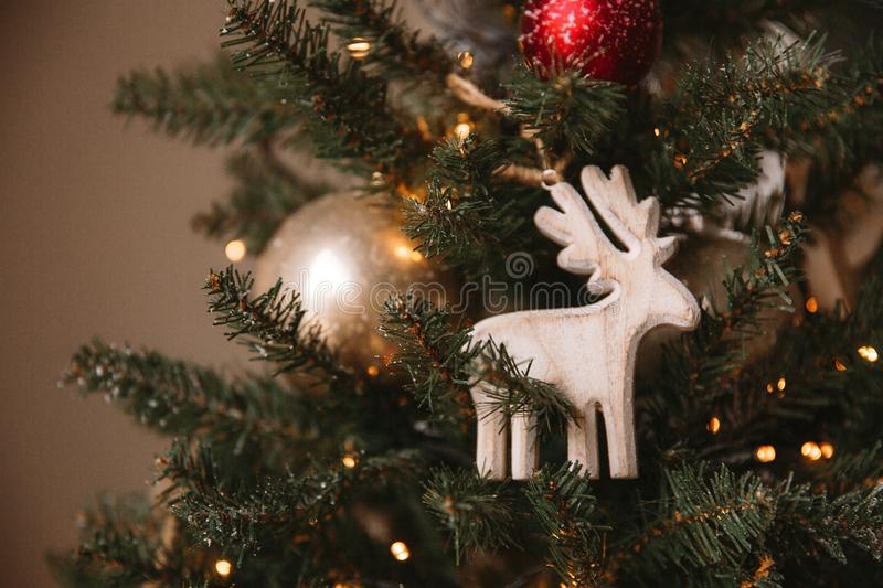Christmas toy wooden deer on the Christmas tree. Near the window stock photos