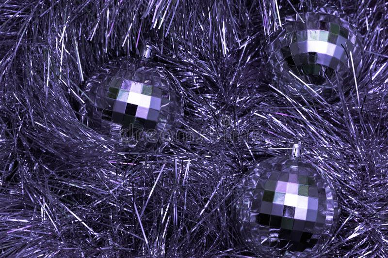 Christmas toys in the form of disco balls lie on a festive silver tinsel, top view, purple color. Tree, glamorous, holiday, background, decoration, shiny stock photo