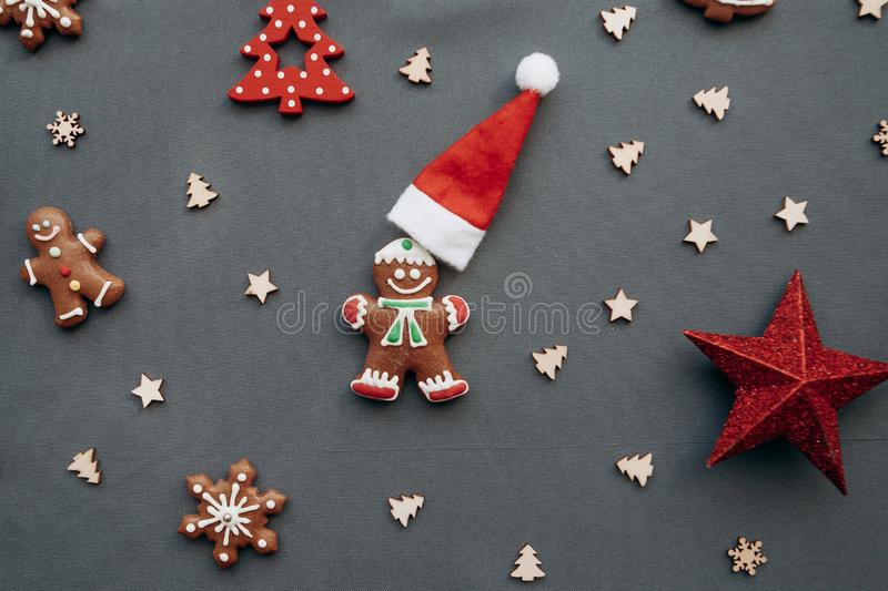 Christmas toys and gingerbread in the form of a traditional ginger man with a Santa Claus hat on a gray background. royalty free stock image