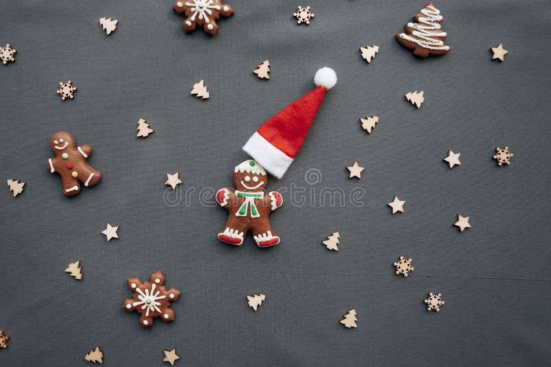 Christmas toys and gingerbread in the form of a traditional ginger man with a Santa Claus hat on a gray background. Christmas or New Year background royalty free stock photo