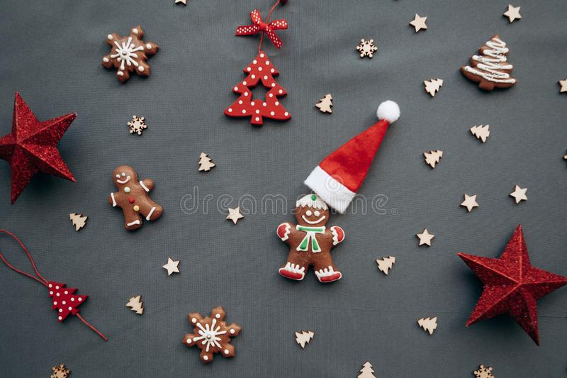 Christmas toys and gingerbread in the form of a traditional ginger man with a Santa Claus hat on a gray background. royalty free stock photo