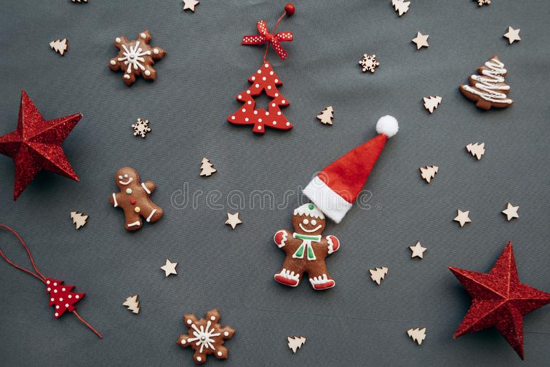 Christmas toys and gingerbread in the form of a traditional ginger man with a Santa Claus hat on a gray background. Christmas or New Year background royalty free stock images