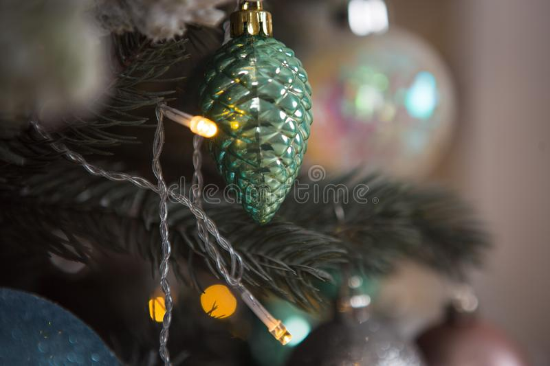 Christmas toys on a green artificial Christmas tree in a gentle style and gold lights garlands. Green, white and blue glass cones and balls decorate the spruce royalty free stock image