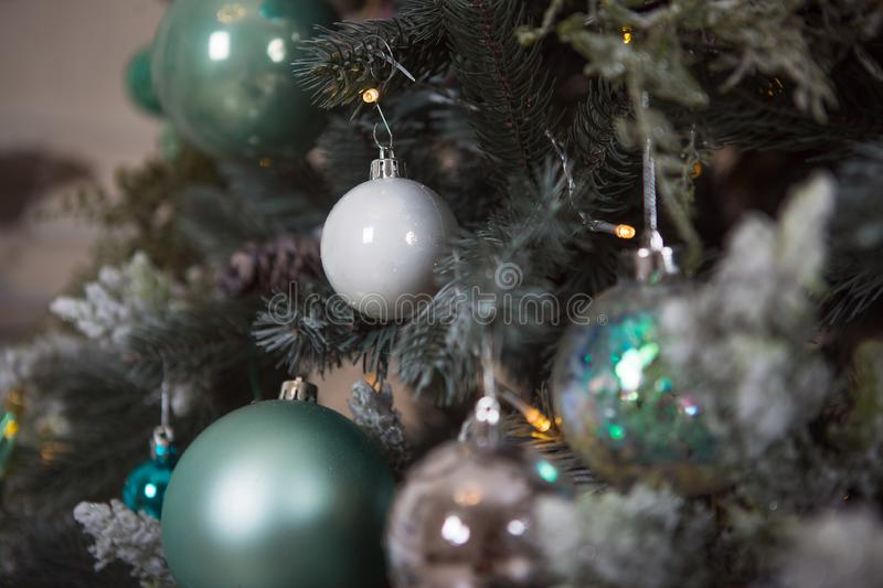 Christmas toys on a green artificial Christmas tree in a gentle style and gold lights garlands. Green, white and blue glass cones and balls decorate the spruce royalty free stock photos